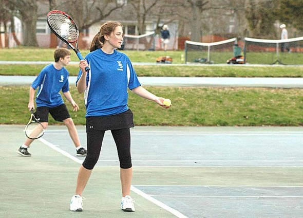 Freshman Kasey Linkhart prepares to serve on the second doubles court in the Yellow Springs High School varsity co-ed tennis team's match against Beavercreek on Wednesday, April 9. Visible behind her on the first double court is sophomore Henry Potts-Rubin. (photo by Megan Bachman)