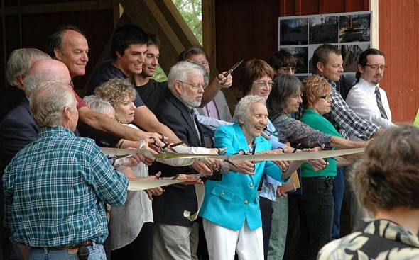 """About 200 people gathered Friday morning, May 9, for the opening and dedication of the new Richard P. Eastman Hyde Road covered bridge. The structure crosses a section of the Little Miami Scenic Trail. Present at the ribbon cutting are Richard Eastman's wife Wilberta """"Billie"""" Eastman, at front, with son John at left. (Photos by Carol Simmons)"""