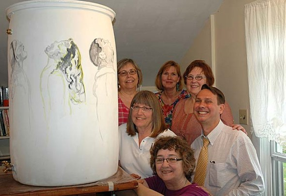 Two recently formed peer-led groups meet locally for those living wih mental illness and their families. With the support of the Village Human Relations Commission, the groups will sell raffle tickets for an artist-decorated rain barrel, shown above, at the May 22 Village manager forum to raise money for Mental Health First Aid training. Shown above are, clockwise from top left, Donna Sorrell, Kathy Adams, Kathryn Hitchcock, Village Council member Brian Housh, artist Sandi Sharp, and Linda Rudawski of the HRC. (Photo by Carol Simmons)