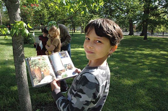 Isaiah Search used a tree identification guide to help his team chart and name the trees near the tennis court at Mills Lawn school on Monday. The second-grade class is mapping the campus to help the district figure out which trees are at risk for emerald ash borer disease. The students will present their maps and leaf rubbings at the MLS project-based learning Exhibition Night, Friday, May 23, at 6:30 p.m. at the school. McKinney and Yellow Springs High School will host their PBL exhibition Thursday, May 22, 6 p.m., at the high school. (Photo by Lauren Heaton)