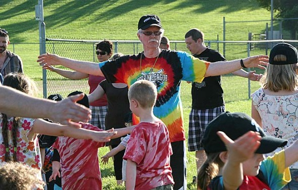 Coach Jimmy Chesire led his enthusiastic young t-ball squad in warm-ups at the opening game of the Perry League season. (photo by Suzanne Szempruch)