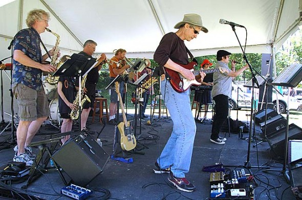 Ohio Brass & Electric, which plays tonight at the Emporium, performed last Saturday at the Yellow Springs Street Fair. Shown in front is guitarist Skip Leeds. The group was joined by 11-year-old Sean McDonald on saxophone.
