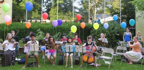 The annual Summer Strings and Band camp always ends with a grand finale concert and cake a balloons. Shirley Mullins conducted this one c. 2010 in Kings Yard.