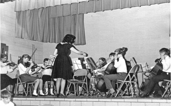 The Yellow Springs Summer Strings and Band Program will celebrate its 50th year as a summer music program for local children with a cello choir for alumni this Saturday, July 5, at 5 p.m., followed by a full orchestra performance. Shown above is an early concert with Summer Strings' founder, Shirley Mullins, who continues to direct the program. (submitted photo)