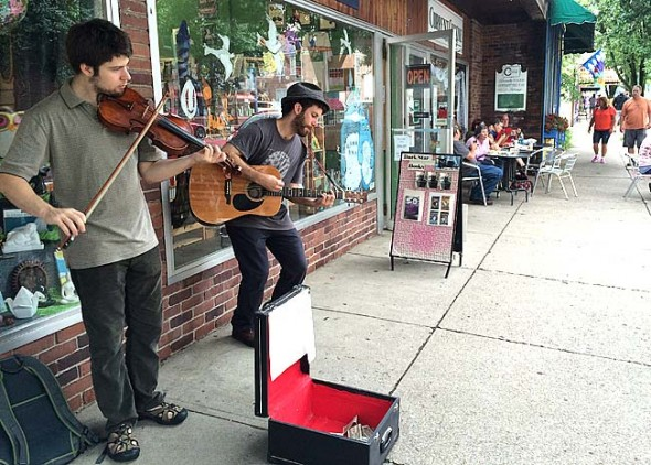 Local street musicians Perin Ellsworth-Heller, left, and Ben Hemmendinger performed their Appalachian and Irish-inspired tunes on the sidewalk along Xenia Avenue for about two hours last Saturday. Village Council passed a new policy this week that limits for how long and where street musicians can play after receiving numerous noise complaints from downtown shop owners and their employees. (Photo by Megan Bachman)
