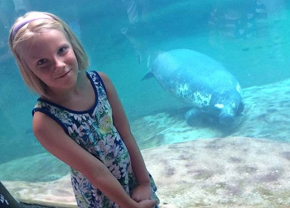 Mackenzie Horton, 9, recently asked friends and family to forego birthday gifts and instead make donations to help save manatees. She raised $160 so far and hopes to raise $200 by mid-August. Mackenzie is shown at the Columbus Zoo with her favorite marine mammal. (Submitted Photo)
