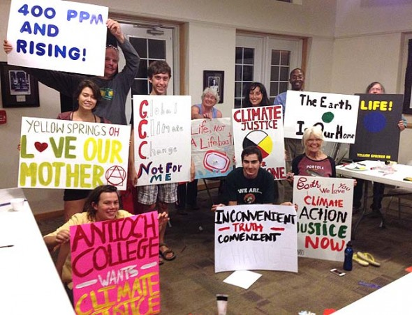 Yellow Springs climate change activists recently made the signs they will carry at the People's Climate March on Sunday, Sept. 21, in New York City in what is projected to be largest climate change protest in history. Pictured are, from left, top row: Olivia Minella, Eric Johnson, Sean Allen, Brenda Goff, Sophie Major, Kevin McGruder, Susan Hirsch; front row, Lauren Gjessing, Baxter Foskuhl, Sylvia Carter Denny.  (Submitted photo)