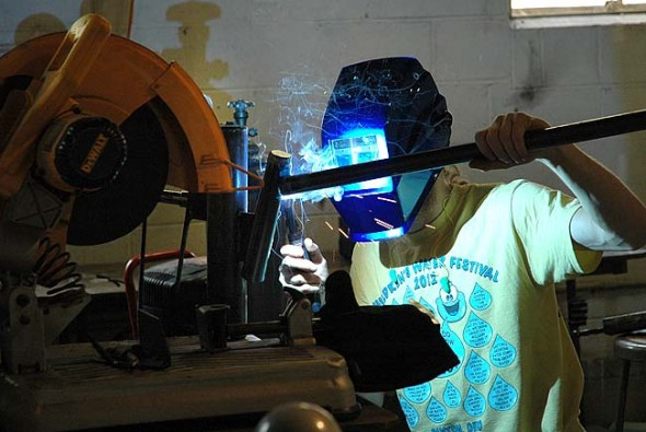 Third-year student Dustin Mapel welds the arm for the turbine in the campus shop, where YS Kids Playhouse was located over the summer. (Photo by Lauren Heaton)c