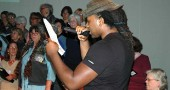Issa Walker, of the Yellow Springs-based hip-hop group Village Fam, rehearses with the World House Choir, under the direction of Catherine Roma, on a song that will be performed as part of Friday night's Pep Rally for Marriage Equality, hosted by the choir, at the Antioch Foundry Theater. The collaborative piece composed specially for the all-volunteer choir combines rap and four-part harmonies. Friday night's multimedia event, scheduled to begin at 7:40 p.m., will include music, dance and a variety of visual elements. In addition to members of Village Fam, guest performers will include MUSE, Cincinnati's Women's Choir; and dancers Melissa Heston and Rodney Veal. Admission is free. (Photo by Carol Simmons)