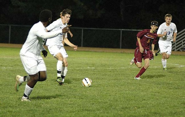 Senior midfielder Jared Scarfpin passed the ball up to forward Joe Plumber during the Yellow Springs High School boys varsity soccer team's 6–0 victory over Northeastern at home in the first round of the sectional tournament. Plumber scored a goal a few minutes later. Also visible is YSHS forward Ian Chick. (Photo by Megan Bachman)