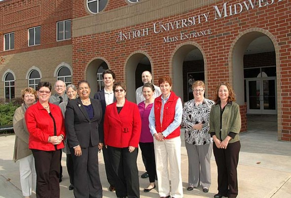 Antioch University offices moved into the AU Midwest building this week. Pictured in front are the administrative staff of both institutions, from left, back row, chair of AUM's Early Childhood Education program Julie Biddle, Enrollment Management Vice Chancellor Ronald Brown, Interdisciplinary Graduate Programs Director Sara Ross, VP of Institutional Advancement Ian Swedish, Library Director Steve Shaw, Marketing Manager Kelly Leff; and front row, School of Education Director Marian Glancy, AUM President Karen Schuster Webb, University Chancellor Felice Nudelman, core faculty member Mary Ann Short, Regional CFO Barbra Stewart, and presidential assistant Jennifer Maynard.  (Photo by Lauren Heaton)