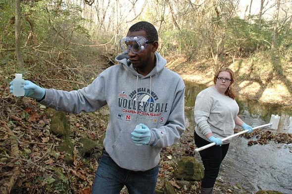 Last month, Wright State University students James Waweru, left, and Sarah Steele tested the water quality of Yellow Springs Creek near the Grinnell Road covered bridge. The Advanced Environmental Chemistry class tested 10 sites in and around Glen Helen Nature Preserve and found high levels of nitrates and E. coli in some springs and surface water and a private well. They will share their results at 3 p.m. Wednesday, Dec. 10, at the Vernet Ecological Center.  (Photo by Megan Bachman)