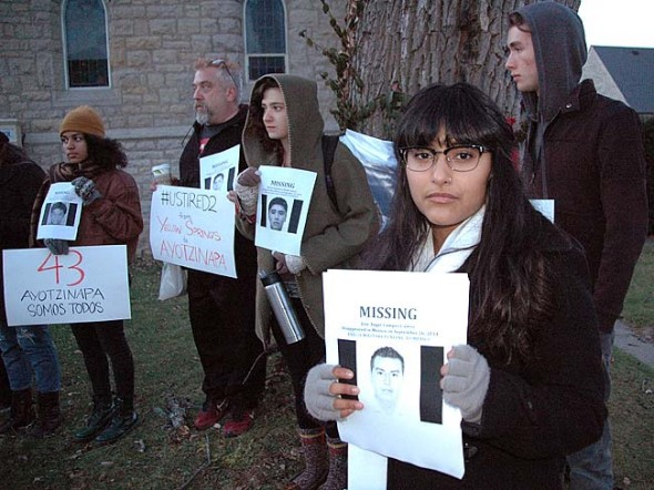 """Odette Chavez-Mayo, in foreground, organized a candlelight vigil Friday, Dec. 3, after she found out about the murders of 43 Mexican students who were headed to a protest. She points out the similarity between police brutality in Mexico and the shooting of an unarmed African-American youth in Ferguson, and notes the need to """"stick together."""" (Photos by Matt Minde)"""