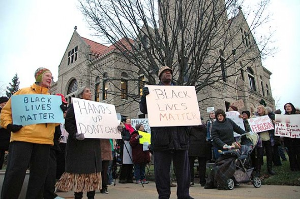 Villagers, from left, Joan Chappelle, Cheryl Smith and Bomani Moyenda, and nearly 100 others attended a demonstration at the Greene County courthouse in Xenia on Monday evening to highlight the injustice of John Crawford's death by police shooting at the Beavercreek Walmart in August.  (Photo by Lauren Heaton)
