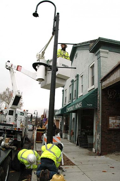 Yellow Springs Electric and Water Distribution Superintendent Johnny Bates, bottom right, and crew members Jeff Horn, bottom left, and Ben Sparks, top, installed several of the Village's new LED streetlamps downtown on Tuesday.