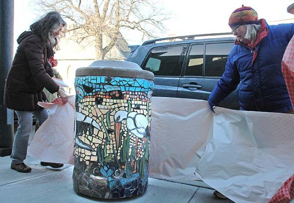 Artists Käthi Seidl, left, and Beth Holyoke unveiled their newly created artistic trash cans downtown last Friday morning, including the stork-themed can outside Sunrise Cafe. The three newly unveiled cans, which join the initial opossum-themed can outside Current Cuisine, will be joined by two other cans soon to complete a pilot project funded by the Village. (Photo by Diane Chiddister)