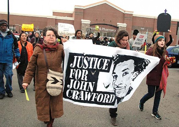 "John and Maria Booth, left, and Liz Porter, center, with Antioch College students Lauren Gjessing and Rachel Humphreys carrying a banner, were among the many villagers who took part in a ""die-in"" protesting the police shooting of John Crawford last Saturday at the Beavercreek Walmart. About 200 protesters took part in the event, which caused Walmart to shut down the store for two hours. (Photos by Diane Chiddister)"