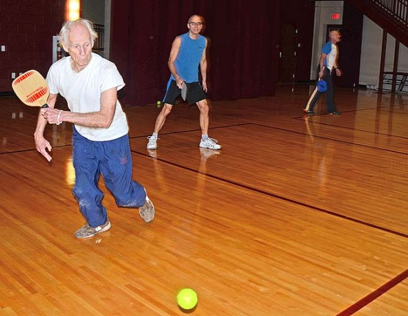 Al Schlueter, left, and Franklin Halley, center, are among the villagers who have caught the bug for pickleball at the Antioch College Wellness Center. A pickup pickleball game takes place every Sunday at 1 p.m. in the South Gym. (Photo by Megan Bachman)