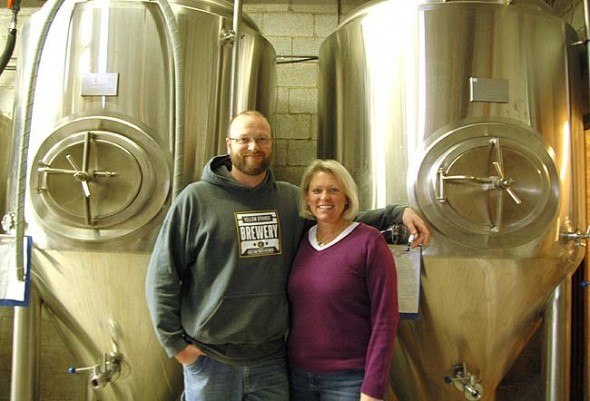 Yellow Springs Brewery owners Nate Cornett and Lisa Wolters will soon be doubling their capacity and adding a canning line at their MillWorks facility. Here they stood with their 15-barrel fermenters, which will be upgraded to 30-barrel fermenters this spring. The brewery started as just a 7-barrel facility. (Photo by Megan Bachman)