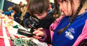 Jonah Simon and Vivian Grushon examine various items up closer with magnifying glasses at the optics station at Mills Lawn School's annual Math and Science Night. (Photos by Matt Minde)