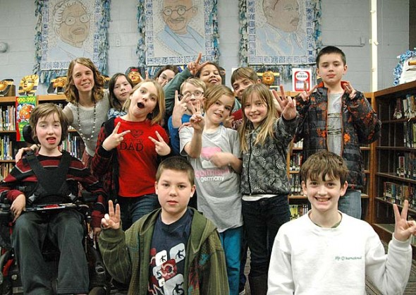 Students in the Mills Lawn Elementary School media club worked on projects for Peace Week, March 16–20, as part of the schoolwide Project Peace, an effort to teach conflict resolution and empathy. Hanging above students are the triptychs of peace leaders created for Project Peace in 2013. Pictured are, from left, front row: Noah Van Hoose and Peter Cooper; second row: Owen Gustafson, Sophie Bottelier, Zoe Hamilton and Hailey Rowe; third row: Aiden Adamson, Ty Housh and Shawn Van Hoose; fourth row: media club facilitator Allison Paul, Lisa Bales, Mila De Spain and Camryn Strolger. (Photo by Megan Bachman)