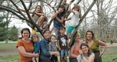 These moms and kids, along with the rest of their families, are among those who will attend Tar Hollow on May 17–19. Pictured on the Mills Lawn playground are, from left in front, Eden Matteson with Violet; Victoria Rowe with Ainslie; Matteo Basora; Corrie Van Ausdal; Karla Horvath; and Alice Basora. In the tree are, from left clockwise, Carina Basora; Tiger Jane Collins (top); Jack Horvath; Hayley Rowe; Ashlea Rowe; and, turning away, Teddy Horvath. (Photo by Diane Chiddister)