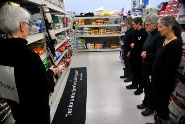 (From left to right) Katie Egart, Terry Snyder, MJ Gentile, Dorothy Smith, and Sandy King stand silently by a banner near the aisle where John Crawford was shot. (photo by Aaron Zaremsky)