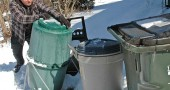 Local recycling expert Tom Clevenger recently tumbled his compost barrel, which he uses to recycle his household's kitchen scraps. Clevenger is working with other villagers to improve the town's poor recycling record and find other ways to reduce and reuse waste here. (Photo by Megan Bachman)