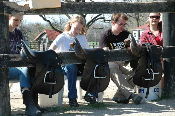 Pictured here are, from left, Anna Williamson, Rachel Hammond, Connor Gravely-Novello and Jennifer Lawson, cleaning saddles at the Riding Centre. (Photo by Lauren Heaton)`
