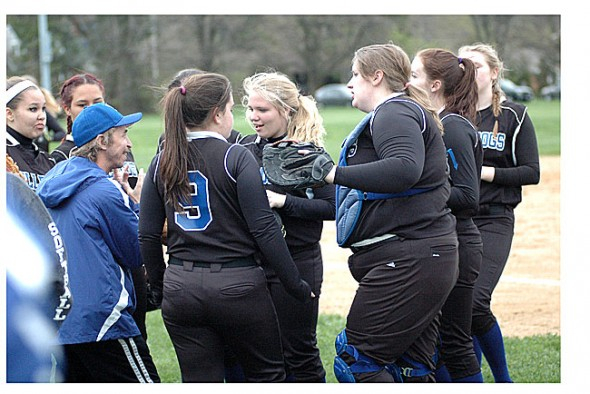 The girls team huddled with Coach Jimmy before taking a turn at bat.