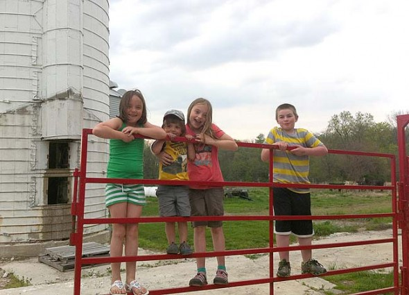 Local kids, from left Rebecca, William and Josie DeWine and Dane Beal hung out with the cows of Whitehall Farm, a 940-acre property just north of the village that was saved from development in 1999. The Tecumseh Land Trust, which played a major role in preserving the land, will host a Family Fun Day at Whitehall on Sunday, May 10, with games, food, historical tours and horse-drawn carriage rides. (Submitted photo by Ara Beal)