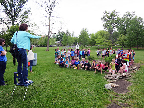 Nan Meekin sets up a photo capturing Mills Lawn 2nd grade students and their butterfly garden