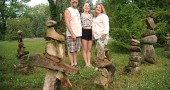 The Village of Yellow Springs Public Art Commission will award Tim and Kelley Callahan, here with their daughter Lucy, the first Village Inspiration and Design Award, or VIDA, on Friday, June 19, 8 p.m. at the YSAC Gallery. At their home on the corner of Corry Street and Glen View Road, the Callahans have built ever-changing stone piles, or cairns, for the last 20 years. (photo by Lauren Heaton)
