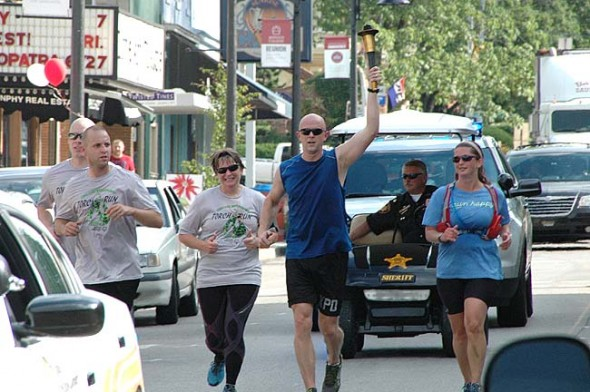 "Captain Steve Lane of the Xenia Police Department ran the ""Flame of Hope"" through downtown Yellow Springs Thursday, as part of the long-standing Law Enforcement Torch  Run fundraiser for the Ohio Special Olympics. (Photo by Matt Minde)"
