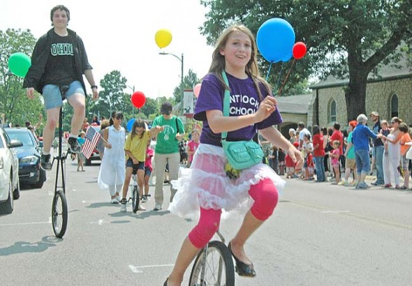 HIGH ROLLERS: Whizzing through the parade downtown, Antioch School student Zay Crawford (front) and alumnus Max Mullin balanced their unicycles (one a giraffe!) between floats, candy throwers and water sprayers.