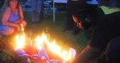 As thousands attended last Saturday's 4th of July fireworks at Gaunt Park, about 30 members of the Greene County Black Lives Matter group burned a Confederate flag in protest of recent church burnings, the Charleston massacre of nine African Americans, and the police shooting last year of John Crawford in the Beavercreek Walmart. Shown above is group member Talis Gage. (Photo by Aaron Zaremsky)