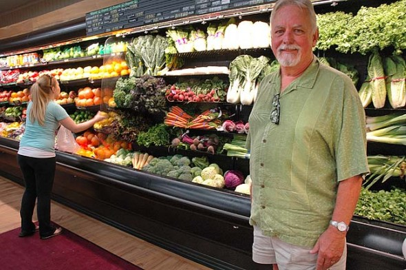 Tom Gray, owner of Tom's Market, has been with the store 50 years, and the store will celebrate the anniversary with free hot dogs on July 17–18. Gray is shown here in the store's produce department, which underwent extensive renovation last year. (Photo by Diane Chiddister)