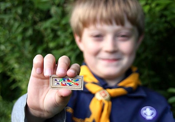 """Cub Scout Bobby Wyatt holds an """"Inclusive Scouting Award"""" distributed by the Scouts for Equality. The unofficial symbolic badge signals a scout is tolerant and inclusive. (Submitted photo by Lake Miller)"""