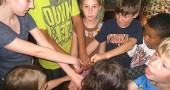 "Ursula Kremer, left, a Youth Helper at this summer's Bahá'í day camp, leads a group of campers in a game called ""The Knot,"" in which children must untangle themselves without breaking hands. The game enacts the virtues of happiness and unity. (Submitted photo)"