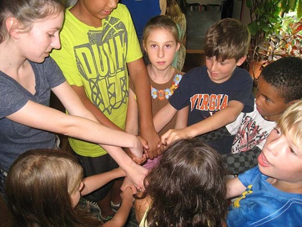 """Ursula Kremer, left, a Youth Helper at this summer's Bahá'í day camp, leads a group of campers in a game called """"The Knot,"""" in which children must untangle themselves without breaking hands. The game enacts the virtues of happiness and unity. (Submitted photo)"""