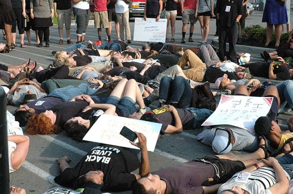 Dozens of people participated in a rally and die-in at the Beavercreek Walmart on Wednesday, Aug. 5, to commemorate the life of John Crawford III, who was killed by police in the store a year ago. The event was organized by Black Lives Matter Miami Valley and included many local residents. (Photo by Dylan Taylor-Lehman)