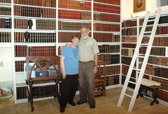 "Jeanne and Hardy Ballantine stand in front of the extensive library of their North Walnut Street home. The couple have lived in Yellow Springs since 1973 and are relocating to Amherst, Mass., to be closer to their three children. Despite the excitement of a new place, bidding goodbye to Yellow Springs isn't easy. ""We've spent most of our lives here,"" Hardy said simply. (Photo by Dylan Taylor-Lehman)"