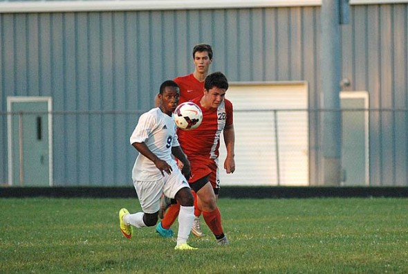 """Junior Levi Jackson thinks on the fly as he follows the ball's trajectory in the Bulldog's home match last Saturday against the Waynesville Spartans. Coach Van Ausdal says the Bulldogs have """"very strong chemistry — they want to win as a team."""" The Match ended in a 2–2 tie. (Photo by Dylan Taylor-Lehman)"""