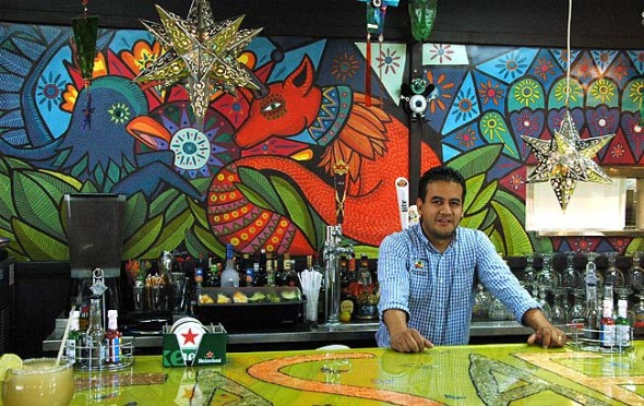 Professional restauranteur Tony Avalos poses behind the bar at Doña Margarota's, a Mexican restaurant that opened last week on Xenia Avenue. The menu is inspired by his grandmother's cooking, he said, and the decor draws influence from whimsical Mexican folk art. Patrons especially appreciated the giant margaritas. (Photo by Dylan Taylor-Lehman)