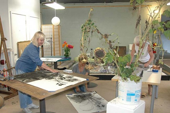 """From left, artists Christine Klinger, Jennifer Rosengarten and Dennie Eagleson captured sunflowers in charcoal at an art sampler class taught by Rosengarten at the Yellow Springs Arts Council (YSAC) last Sunday, Sept. 20. The class drew its inspiration from """"The Sunflower Show,"""" now on display at the YSAC gallery. (Photo by Audrey Hackett)"""
