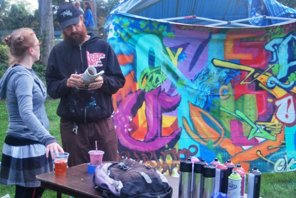 """Christopher Etch stands before his creation - a graffiti mural that spells out """"Cyclops"""". (Photo by Aaron Zaremsky)"""