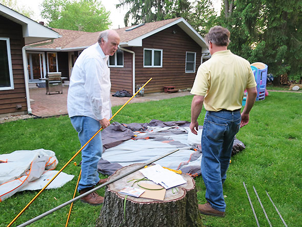 the men confer on tent assembly
