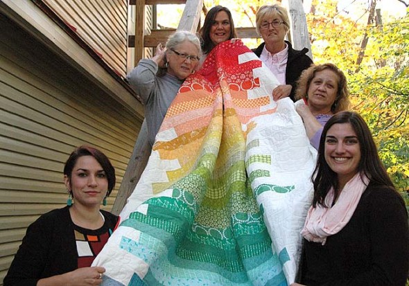 Anna Haller, lower right, created this rainbow-colored quilt for the newly formalized Village Assistance Network to raffle this fall. VAN continues the work of the informal $10 Club started by Chrissy Cruz to meet emergency financial needs in the village. Pictured around the quilt are the group's board members, clockwise from left: Lindsay Burke, Kate Anderson, Wendy Ricks, Jane Nipper and Cruz. (Photo by Carol Simmons)