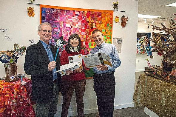 """Yellow Springs Arts Council launched Art Roulette this week, a campaign to raise $30,000 by matching donors with """"creative sparks"""" to artists who will make those ideas come alive. From left, YSAC board member Timothy Barhorst, gallery coordinator Nancy Mellon and President Jerome Borchers (with art by Sharri Phillips) are among the campaign organizers. (Photo by Audrey Hackett)"""