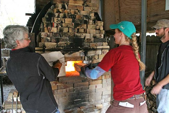 Nicki Strouss fed the fire while Carol Culberston held open the kiln door and Brad Husk passed over the wood. (photo by Suzanne Szempruch)